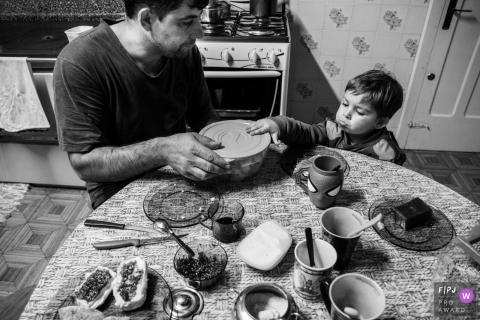 Un petit garçon pousse quand son père refuse de lui ouvrir un contenant de nourriture dans cette image familiale de style documentaire enregistrée par un photographe du Rio Grande do Sul, au Brésil.