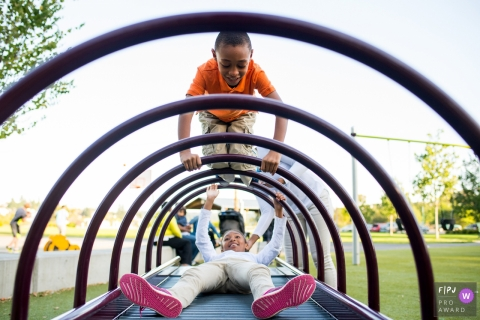 Two children play on curved bars on a playground in this Family Photojournalist Association contest awarded photo created by a Washignton family photographer.