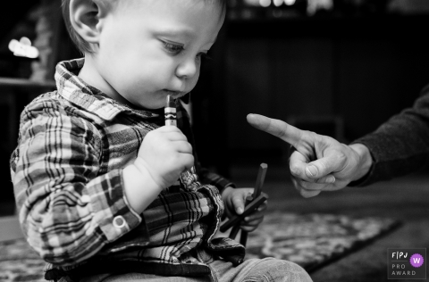 A parent wags their finger at a little boy who is about to put a crayon in his mouth in this FPJA award-winning picture by a Washington family photographer.