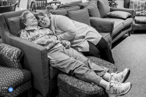 Two women relax on a sofa together in this family picture by a Connecticut photographer.