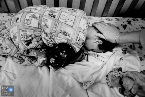 A mother pats her son's head as he lays in his crib  in this photograph by a Key West, FL documentary family photographer.