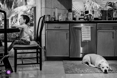 Un chien est allongé sur le sol derrière un petit garçon qui déjeune à la table de la cuisine dans cette photo récompensée par une photo de famille par un photographe de famille documentaire de Key West, en Floride.