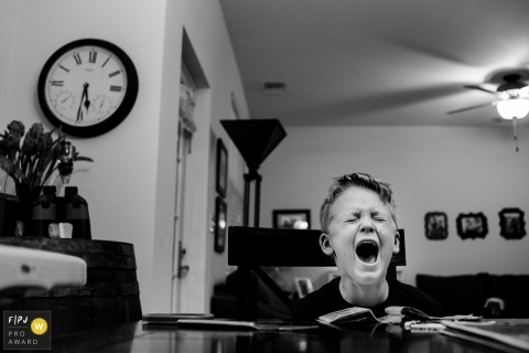 A little boy cries as he sits at a table  in this FPJA award-winning image captured by a Key West, FL family photographer.