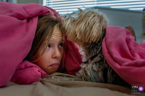 A girl makes a face as she peeks out from under her covers and is met with a kiss from her dog in this award-winning photo by a Key West, FL family photographer.