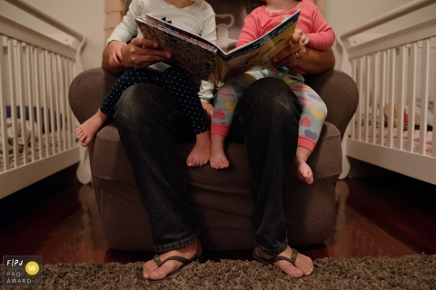 Two little girls each sit on one of their father's knees as he reads them a book  in this image created by a Key West, FL family photographer.