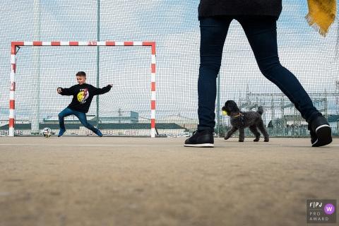 Une famille et son chien jouent au football dans cette photo de famille de style documentaire prise par un photographe d'Anvers.