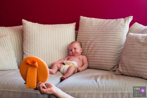 Un bébé est assis sur un canapé et sourit pendant que sa mère lui montre une image de cette photo de famille réalisée par un photographe d'Anvers.