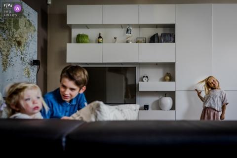 Un frère et une sœur sont assis sur le canapé, tandis que leur autre sœur remue les cheveux en arrière-plan sur cette photo réalisée par un photographe de famille documentaire du Limbourg.