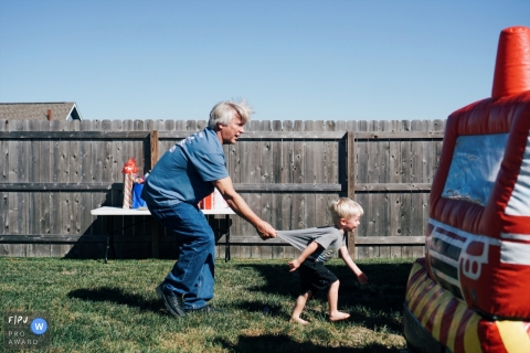 A man pulls a young boy back by his shirt when he tries to enter a bounce house in this Family Photojournalist Association awarded photo by a Kansas City, MO documentary family photographer.