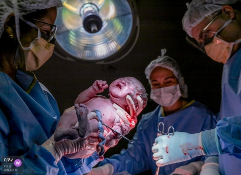 A doctor holds a newborn and prepares to cut the umbilical cord in this image recorded by a documentary-style Salvador birth photographer.