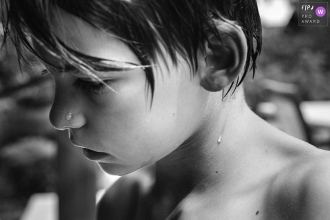Black and white photo of a boy who has just gotten out of a pool, recorded by a Paris, France award-winning, documentary-style family photographer.