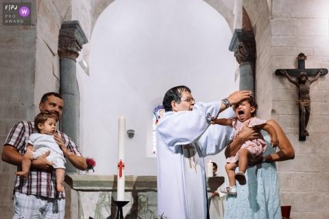 Un prêtre tente de bénir une petite fille malheureuse alors que sa mère la tient sur cette photo réalisée par un photojournaliste de la famille de Paris, en France.