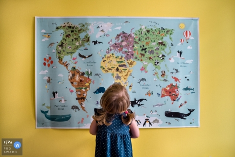 A little girl stares up at a map of the world in this Family Photojournalist Association contest awarded photo created by a Berlin, Germany family photographer.