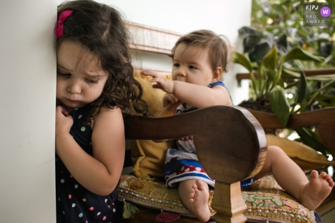 Une petite fille se tient contre un mur alors que sa petite sœur tend la main depuis une chaise sur cette photo primée du FPJA par un photographe de la famille Minas Gerais.
