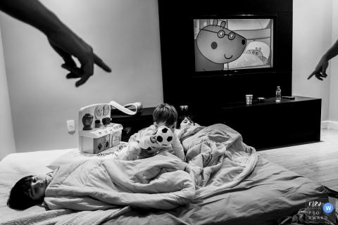 Un garçon est allongé sur son lit alors que son frère rampe sur lui avec un ballon de football en peluche dans cette photo de famille au style documentaire prise par un photographe de Minas Gerais, au Brésil.