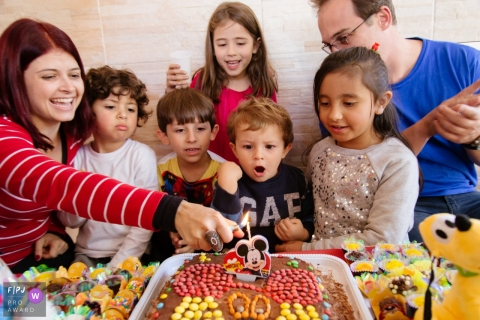 A little boy waits excitedly as his mother lights the candle on his birthday cake in this family picture by a Sao Paulo, Brazil photographer.
