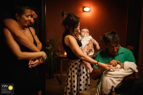 A family gathers around two newborns in this photograph by a Pernambuco, Brazil documentary family photographer.