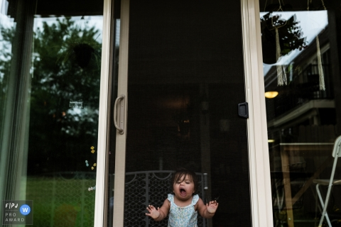 A little girl makes faces on a screen door in this Family Photojournalist Association awarded photo by an Overland Park, KS documentary family photographer.