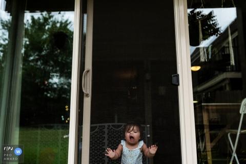 Une petite fille fait des grimaces sur une porte moustiquaire dans cette photo récompensée par la photo par un photographe de famille documentaire du Overland Park, KS.