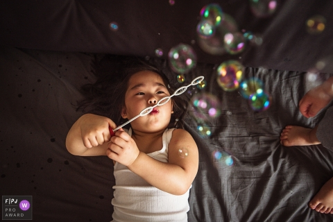 A little girl blows bubbles while she lays in bed in this FPJA award-winning image captured by a Shanghai, China family photographer.