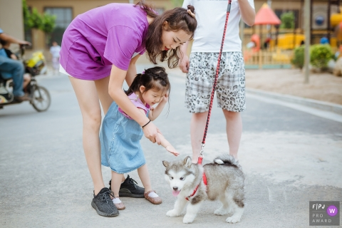 A mother helps her daughter pet a puppy in this image created by a Shanxi, China family photographer.