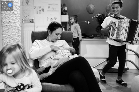A boy plays the accordion while his mother breast feeds his baby sibling in this photo recorded by a Ljubljana award-winning, documentary-style family photographer.