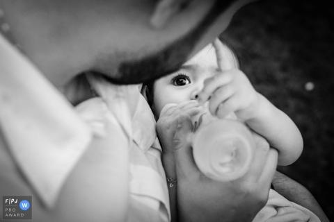 Une bouteille père nourrit son bébé dans cette image de famille de style documentaire enregistrée par un photographe de Minas Gerais, Brésil.