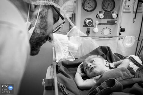 Un père rend visite à son nouveau-né à l'hôpital dans cette image en noir et blanc capturée par un photographe de naissance de style documentaire, Minas Gerais.