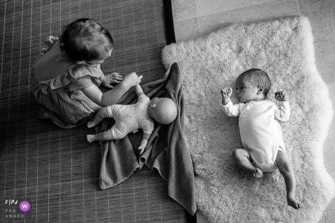 Un bébé regarde sa sœur jouer avec une poupée dans cette photo de famille au style documentaire prise par un photographe savoyard.