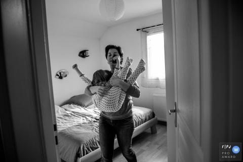 une mère tente de porter sa fille peu coopérative dans cette photo de famille réalisée par un photographe savoyard.