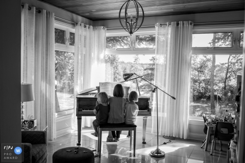 Three children sit at a piano together in this award-winning photo by a Montreal, Quebec family photographer.
