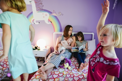 Two girls stand on the end of the bed where their mother and two other siblings read a book in this image created by a Montreal, Quebec family photographer.