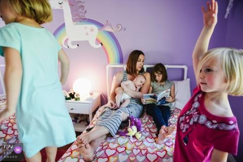 Deux filles se tiennent au bout du lit, là où leur mère et deux autres frères et sœurs lisent un livre illustré par une photographe de famille de Montréal, au Québec.