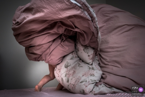 Un enfant joue avec les draps de lit sur cette image capturée par un photojournaliste de la famille Bath.