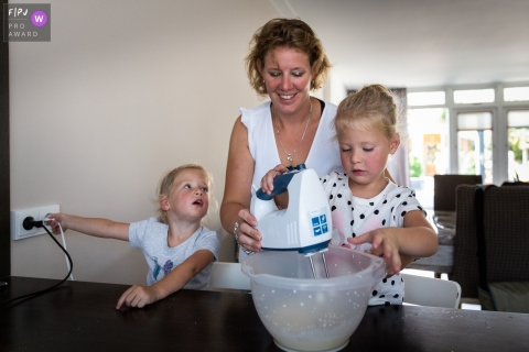 Two girls help their mother in the kitchen as she helps one of them use a mixer in this photo by a Netherlands award-winning family photographer.