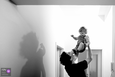 Un père élève son fils haut dans les airs dans cette image primée d'un prix FPJA par un photographe de famille de Berlin, Allemagne.