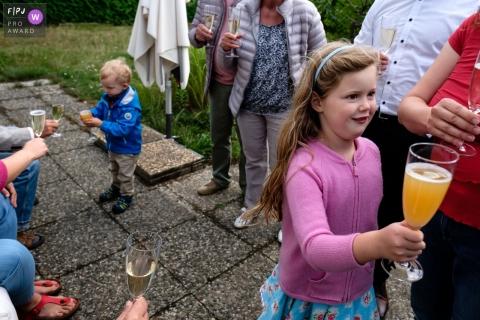 Une famille apprécie le champagne à l'extérieur, alors que deux enfants boivent du jus dans des verres de champagne dans cette photo de famille au style documentaire prise par un photographe de Berlin, en Allemagne.