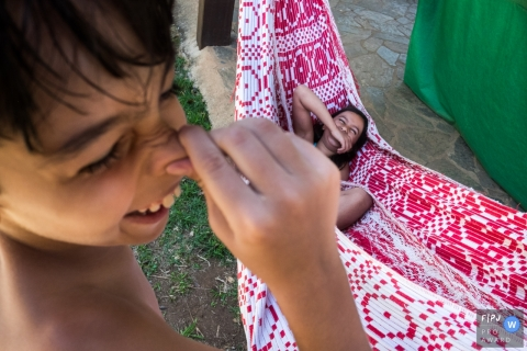 A boy holds his nose as his sister lays laughing in a hammock in this photograph by a Minas Gerais documentary family photographer.