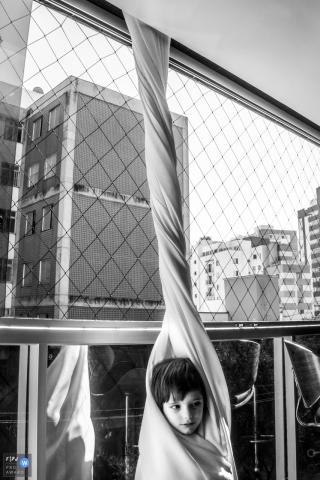 Un petit garçon s'est enveloppé d'un rideau dans cette photo primée par l'Association de photojournalistes de famille par un photographe de famille du documentaire Minas Gerais.