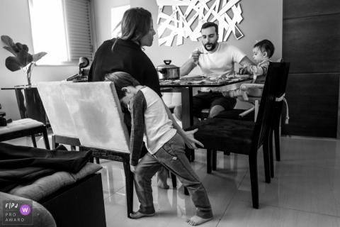 Un petit garçon s'ennuie pendant que ses parents et son petit frère mangent dans cette image primée du FPJA, capturée par un photographe de la famille Minas Gerais.