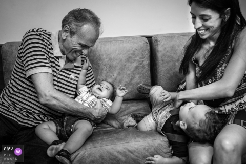 A mother and grandfather play with two baby boys on a couch in this award-winning photo by a Rio de Janeiro, Brazil family photographer.