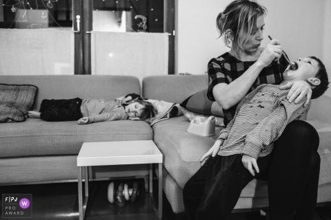 Une mère brosse les dents de son fils pendant que sa fille dort sur le canapé sur cette photo prise par un photographe de famille de style documentaire primé à Anvers.