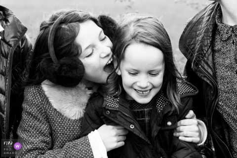 A girl holds her sister as they sit outside between their parents in this photograph created by a London, England family photojournalist.