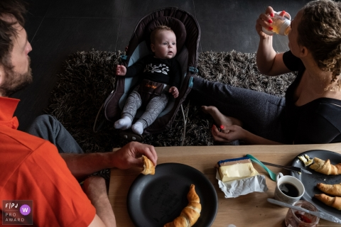 A baby watches as his mother and father eat breakfast in this FPJA award-winning picture by a Gelderland, Netherlands family photographer.