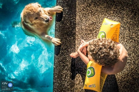 Un garçon assis au bord d'une piscine regarde son chien nager dans cette photo de famille réalisée par un photographe de Sao Paulo, Brésil.