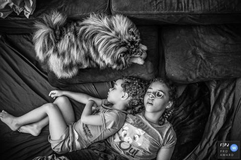 Deux frères et soeurs dorment côte à côte tandis que leur chien les dépose sur cette photo réalisée par un photographe de famille de documentaires de Sao Paulo, Brésil.