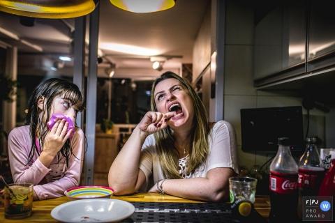 Une jeune fille regarde sa mère en train de se mordre les dents dans cette photo primée de l'Association de photojournalistes de famille par un photographe de famille documentaire de Sao Paulo, Brésil.