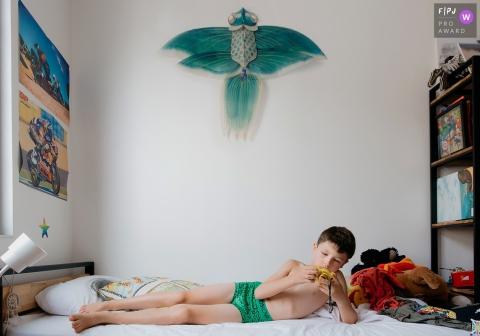 Un garçon regarde sa caméra alors qu'il est couché sur une photo primée d'un photographe de la famille de l'Hérault.