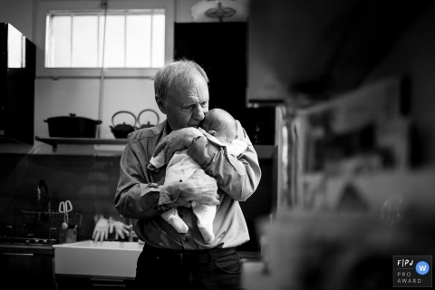A grandfather holds his infant grandchild in this image created by a Herault family photographer.
