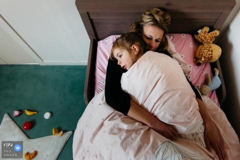 Une fille couche dans son lit avec sa mère sur cette photo enregistrée par un photographe de famille de style documentaire primé dans le département de l'Hérault.